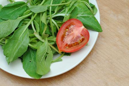 tomato slice: tomato slice and green lettuce on plate