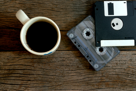 Floppy disk: cup of coffee  cassette tape and floppy disk over wooden floor
