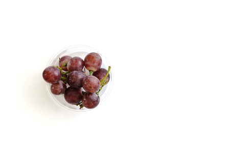 grapes in a plastic cup on white  background