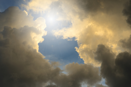 White and dark clouds with sun light against blue sky. Stock Photo