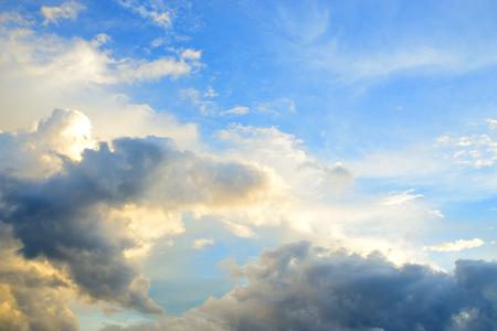 White and dark clouds against blue sky.