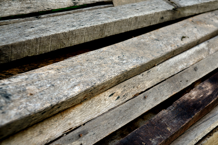 Pile of old used timber planks. Selective focus. Stock Photo