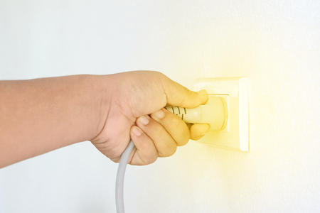 Hand putting electrical plug Into socket on white cement wall. Stock Photo