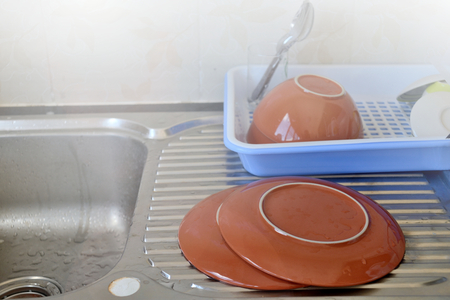 Clean dishes put near the sink in kitchen.