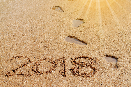 2018 inscription on the sand and footprints with sun flare.
