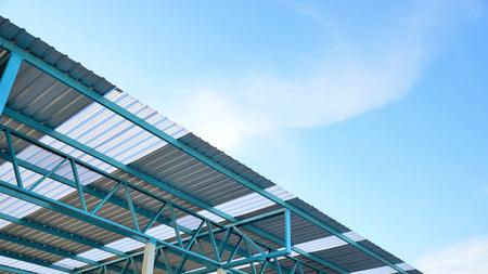 青空と白い雲を持つ金属板屋根の鉄骨構造。 写真素材