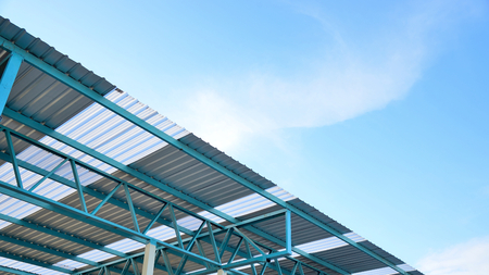 Steel frame structure of metal sheet roof with blue sky and white clouds.