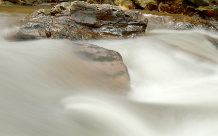 Water flowing fast with stream over the rock.