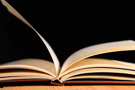 Book was open on wooden table and black background.