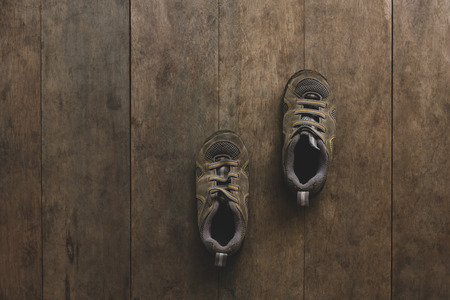 Brown running shoes laid on wooden floor. 스톡 콘텐츠