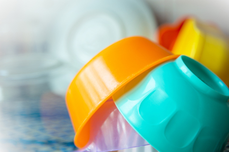 A stack of colorful plastic bowls on the shelf.