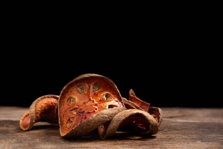 Dried bael fruit on wooden floor.