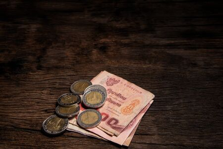 Thai bath banknotes and coins on wooden floor. Banque d'images