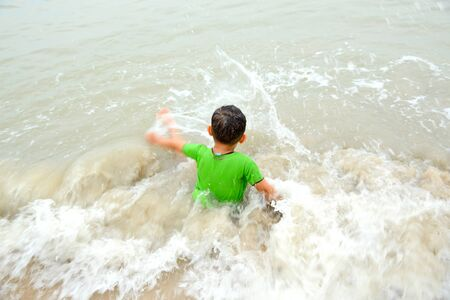 Boy playing on the beach on summer holidays. Banque d'images