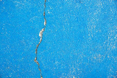 Background of a blue painted cement floor with crack. Closeup from outdoor sports ground.