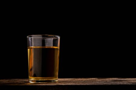 Glass of orange water on wooden table with black background.