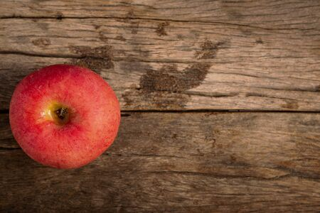 Red apple on wooden table.