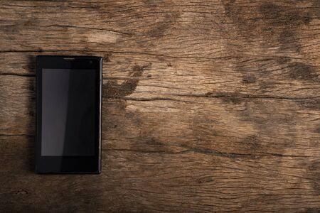 Black smartphone is lying on the wooden table.