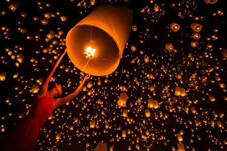 floating: Young woman release sky lanterns to worship buddhas relics in yi peng festival, Chiangmai thailand Stock Photo
