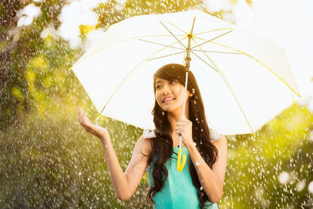 Pretty young asian girl in the rain with umbrella Stock Photo