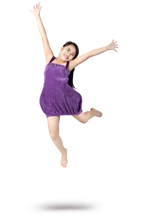 Adorable and happy little asian girl jumping in air, Isolated over white Stockfoto