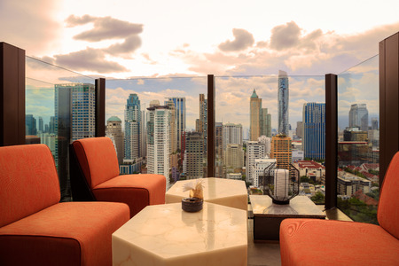 gass: Lobby area of a hotel which can see cityscape at sunset, comfortable sofa unit in front of panoramic view windows overlooking the cityscape with outdoor patio Stock Photo