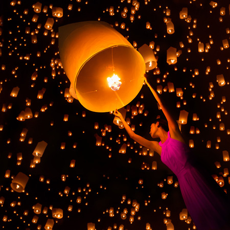 newyears: Young woman release sky lanterns to worship buddhas relics in yi peng festival, Chiangmai thailand Stock Photo