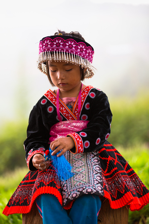 CHIANG MAI, THAILAND - OCT 1 : Akha girl with traditional clothes and silver jewelery in akha hitt tribe minority village on October 25, 2014 in Chiang Mai, Thailand.