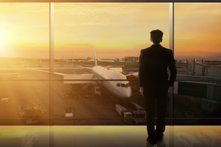 Businessman Waiting In An Airport Lounge With A Scenery Of Departing Airplane Stok Fotoğraf