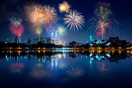 花火、反射水であるクアラルンプール市街の夜景 写真素材