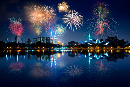 Night view of kuala lumpur city with fireworks and reflection in water