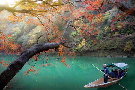 punting: KYOTO, JAPAN - NOVEMBER 24: Boatman punting the boat for tourists to enjoy the autumn view along the bank of Hozu river in Arashiyama area on November 24, 2015 in Kyoto, Japan.