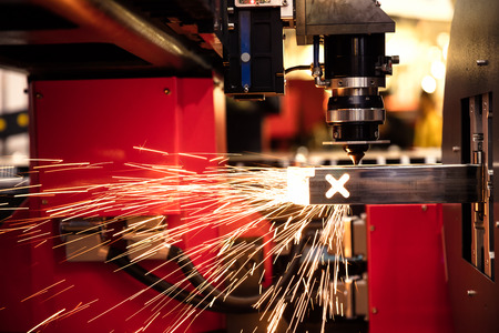 Cutting of sheet metal. Sparks fly from laser by automatic cutting CNC, PLC machine. fabricate work, factory, production