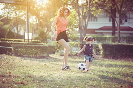 Young mother with daughter playing soccer, Outdoor portrait