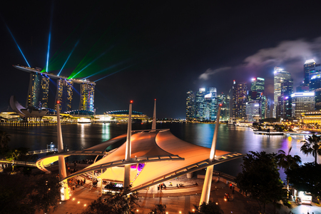 Singapore city skyline at night with laser show.