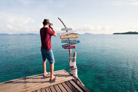 Asian man photographer take photo of tropical island beach and wild sea landscape Stock Photo - 105706143