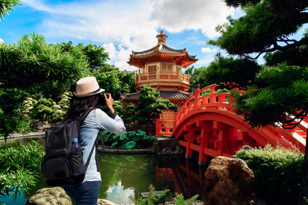female traveler photographing with green backpack and hat enjoying the Golden pagoda of Nan lian garden view. traveling in Hong Kong