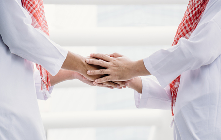 Two Arab young men are shaking hands to greet.