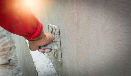 Construction workers in industrial buildings are plastering to build walls. Background image Industrial workers with plastering tools. Home improvement Professional quality concepts of the construction industry with skilled workers.