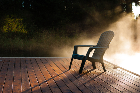 Solitary Adirondack chair on a wooden dock on a foggy morning Stock fotó