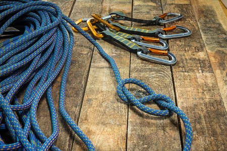 recreational climbing: Climbing rope and carabiner on wooden boards. Four carbine. The node at the end of the rope