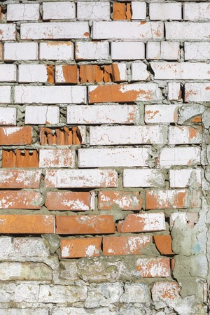 dumps: Texture of old brick wall. Dumps paint and plaster, broken bricks. Bright sunlight