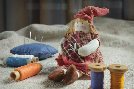 rag doll: Rag Doll and sewing items. The table is covered with a rough cloth. Doll, spools of thread and needles Stock Photo