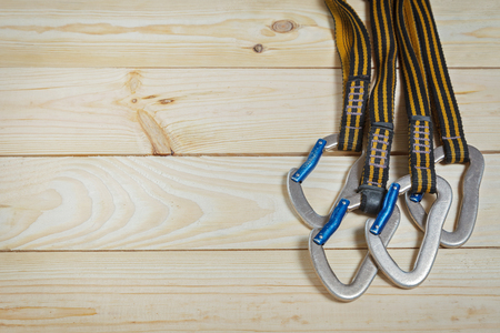 slings: Equipment for mountaineering and rock climbing. On a wooden surface, pine boards. Slings with carabiners Stock Photo