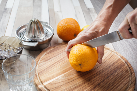 Man with a knife cuts the orange. On the table, a wooden board with fruit and hand juicer for citrus Stock Photo