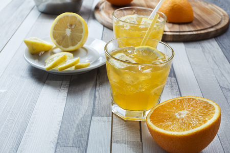 The cooled drink with fresh lemon and orange. On the table two glasses with a drink and fresh fruit Stock Photo