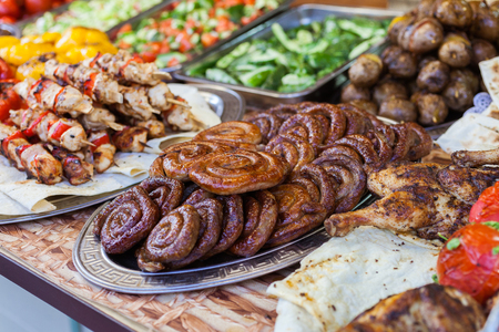 seller: Counter with dishes of grilled sausages and shish kebabs Stock Photo