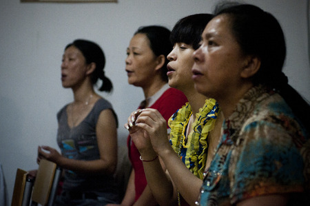 SERBIA, BELGRADE - JULY 23, 2012: Chinese women saying a prayer in the Chinese Baptist Church in Belgrade suburb Ledine. Baptist Christians are a religious minority both in China and Serbia