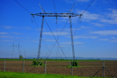 High-voltage tower and cables in agricultural fields against blue sky background