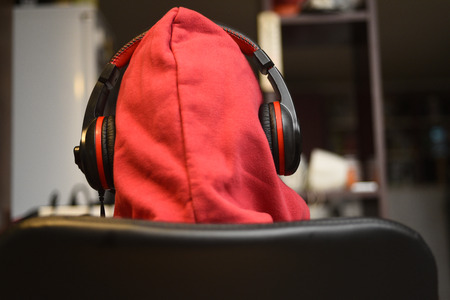 Back view of hooded unidentifiable male person with headphones